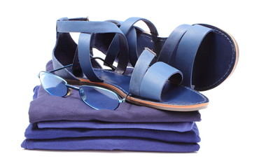 Womanly sandals and sunglasses on pile of blue clothes.