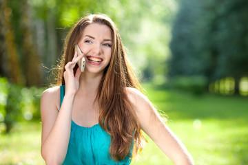Красивая девушка с разговаривает по телефону на природе
