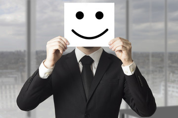businessman holding smile face sign in front of his face