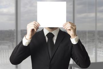 businessman hiding face behind paper