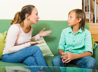 Serious   mother and  teen boy talking in home