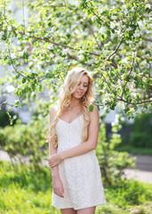 Lovely girl in white dress in summer, enjoying warm sunny day