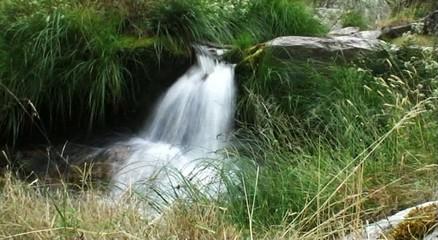 Bonita cascada dentro de un bosque con rocas de granito