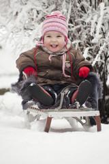 Радостный ребёнок сидит на санках. Снежный фон