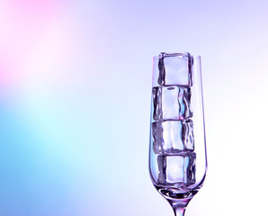 Glass with ice cubes on color background