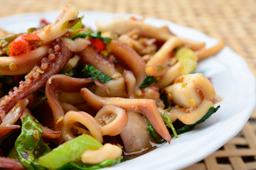 stir-fried squid and basil on white plate and blur bamboo basket