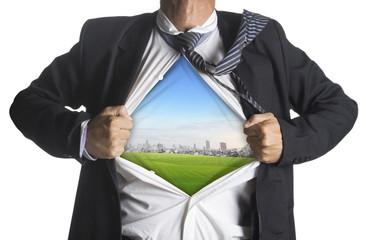 Businessman showing a superhero suit underneath green grass