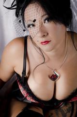 Tätowierte junge Frau in Dessous mit Hut