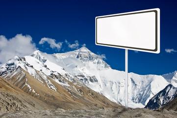 Blank billboard surround by mountain range.