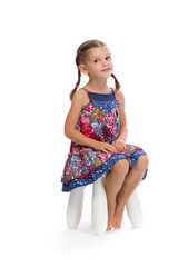 Little girl in a colored dress on a chair in the studio and shy