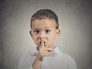 Boy placing finger on lips showing quiet gesture grey background