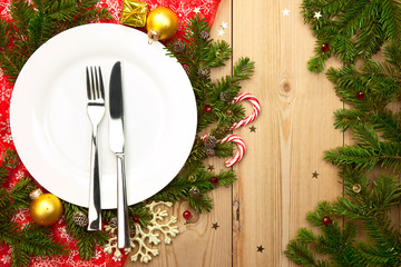 Christmas Dinner - white plate with cutlery on wooden background