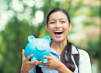 Happy young businesswoman holding piggy bank
