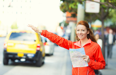 Girl calling yellow taxi cab in New York City, street traffic