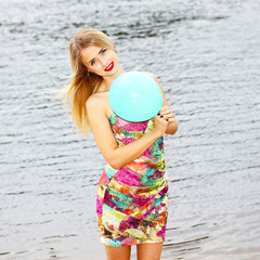 Happy young woman having fun with colorful latex balloon