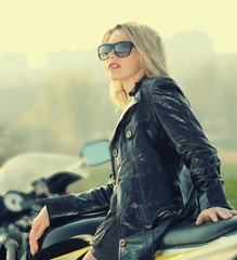 beautiful blonde woman on a sports motorcycle. Urban life style.