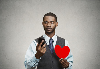 Man checking his smart phone, holding red heart, grey background