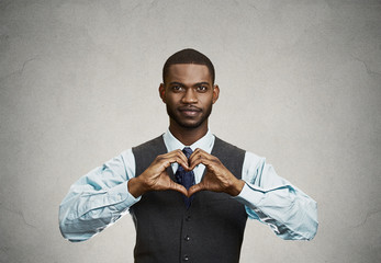 Happy man makes heart using fingers, grey wall background