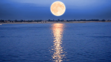 Supermoon rising over river