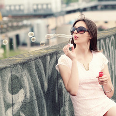 Hipster girl blows bubbles on the roof.