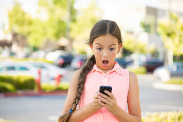 Shocked child texting on mobile, smart phone, outside background