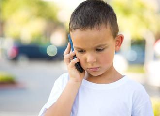 Sad boy talking on mobile phone, outdoors background