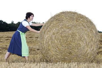 Woman rolling straw bale