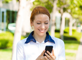 Happy woman texting on smart phone, outside background