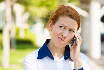Unhappy woman talking on a phone, outside background