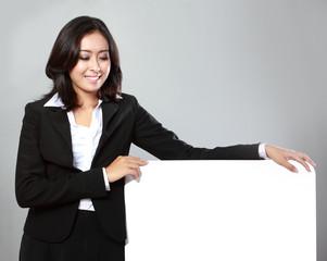 beautiful businesswoman holding blank billboard