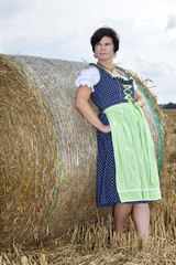 Woman standing on straw bales and enjoys the outdoors