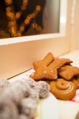 Gingerbread cookies on a window with christmas lights in bokeh