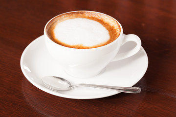 Cup of cappuccino or latte coffee on wood.