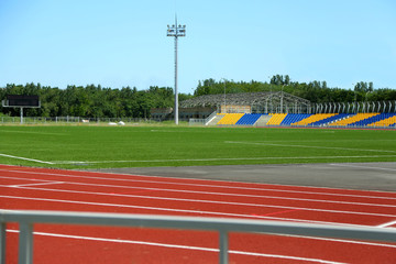 Empty stadium arena with football field and running tracks