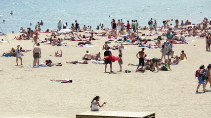 People sunbathing on Barceloneta beach in Barcelona