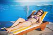 Woman relaxing near blue swimming pool