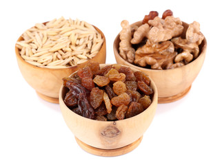 Small wooden bowls with raisins, walnuts and oats isolated