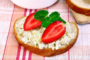 Bread with curd and strawberries on red napkin