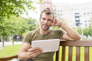 Portrait of smiling casual man looking tablet computer in the st
