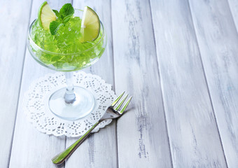 Green jelly with mint leaves in glass on wooden background