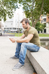 Casual man sitting in the street and holding tablet computer.