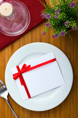 Plate with card with red bow on wood table