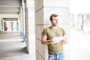 Casual modern man with tablet computer in the street looking awa