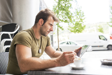 Man sitting in the terrace bar with coffee cup and laptop tablet