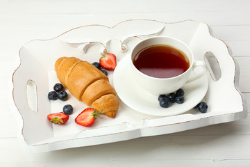 Delicious breakfast with cup of tea, fresh croissant and