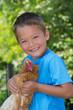 Lachender Junge mit Huhn auf dem Arm