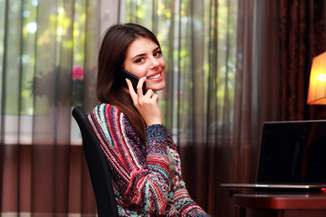Portrait of a smiling woman talking on the phone at home