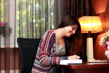 Happy female student doing homework at home