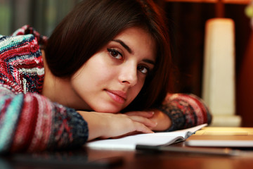 Attractive woman lying on the table with notebook at home