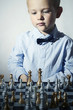 Little boy playing chess.Smart kid.Chessboard.fashion children
